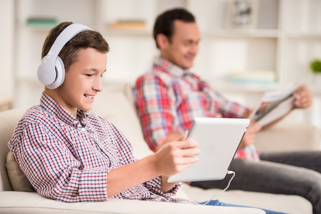 Rapaz sentado no sofá em casa e ouvir música. Foto Premium