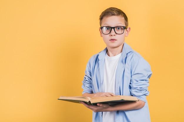 Rapaz sério usando óculos segurando um livro aberto na mão, olhando para a câmera contra um fundo amarelo Foto gratuita