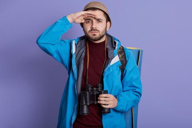 Rapaz, turista, alpinista com mochila e tapete de viagem, vestindo jaqueta e chapéu, fica com binóculo no pescoço Foto gratuita