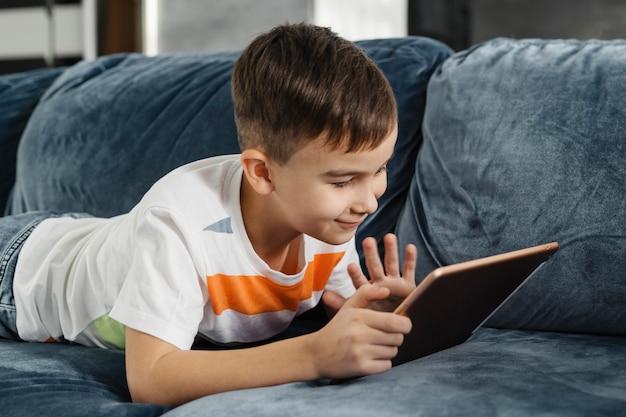 Rapaz, uma casa acenando para alguém no tablet digital Foto gratuita