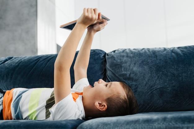 Rapaz, uma casa deitada no sofá e usando tablet digital Foto gratuita
