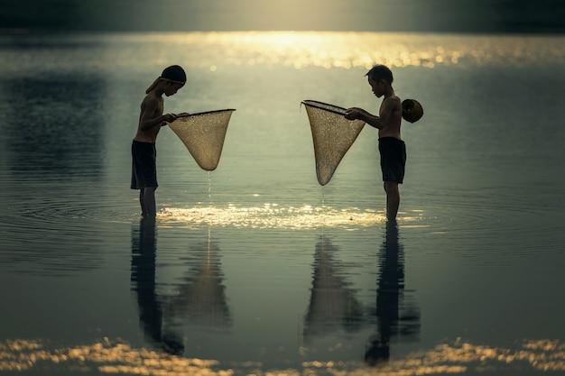 Rapazes asiáticos a pescar no rio Foto Premium