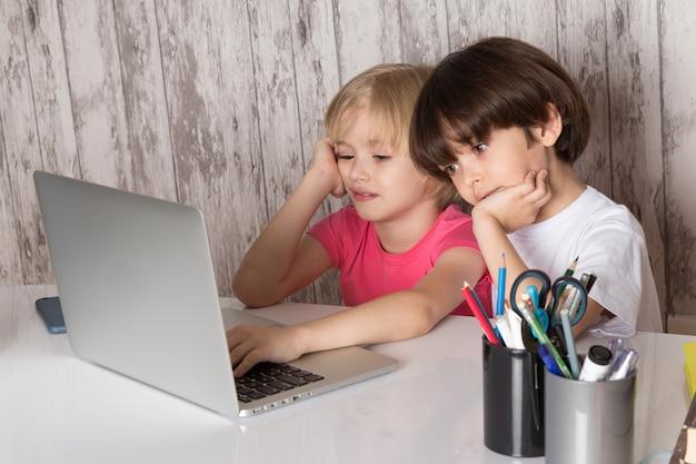 Rapazes giros em camisetas rosa e brancas, usando o laptop cinza em cima da mesa com canetas em fundo cinza Foto gratuita