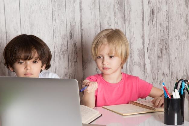 Rapazes giros em camisetas rosa e brancas, usando o laptop cinza em cima da mesa Foto gratuita