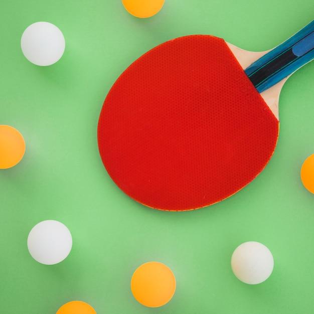 Raquete de ping-pong vermelho com bolas brancas e laranja em fundo verde Foto gratuita