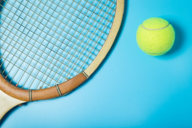 Raquete e bola de tênis no fundo azul. equipamento esportivo. lay plana. Foto Premium