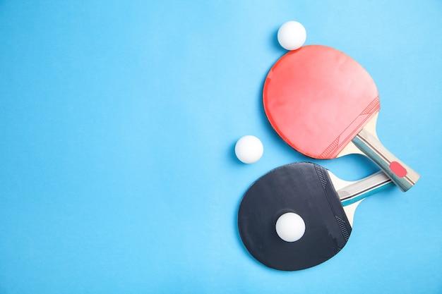 Raquetes de tênis de mesa e bolas de plástico brancas em plano azul e plano Foto Premium