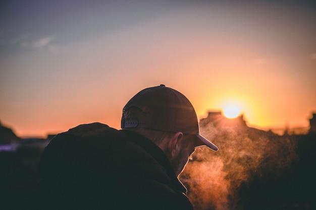 Raso foco na foto das costas de um homem usando boné durante a hora dourada do pôr do sol. Foto gratuita