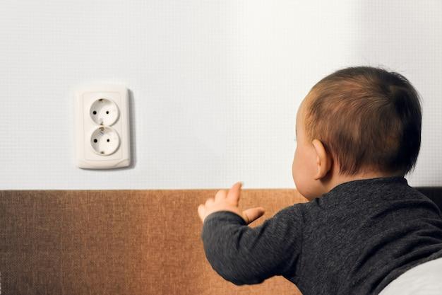 Rastejamento de criança colocar dedos tomada elétrica tomada de parede risco perigo casa conceito de segurança Foto Premium