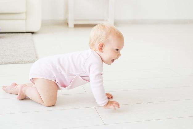 Rastejando menina engraçada dentro de casa em casa. Foto Premium