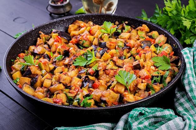 Ratatouille. ensopado de berinjela vegetariano, pimentão, cebola, alho e tomate com ervas Foto Premium