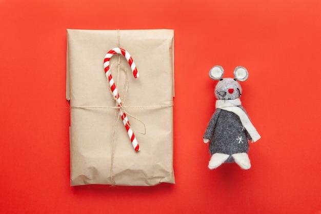 Rato de brinquedo cinza, símbolo de 2020 no calendário chinês e presente de natal embrulhado em papel ofício Foto Premium