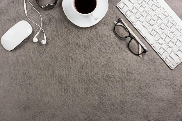 Rato; teclado; xícara de café; fone de ouvido; relógio de pulso em fundo cinza Foto gratuita