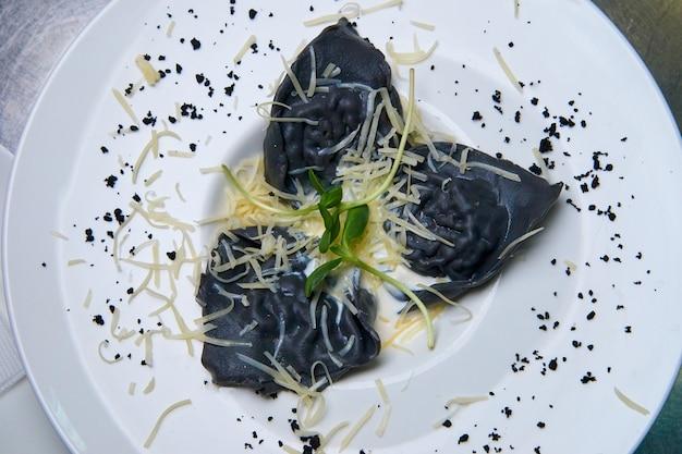 Ravioli com tinta de choco, molho e queijo. Foto Premium
