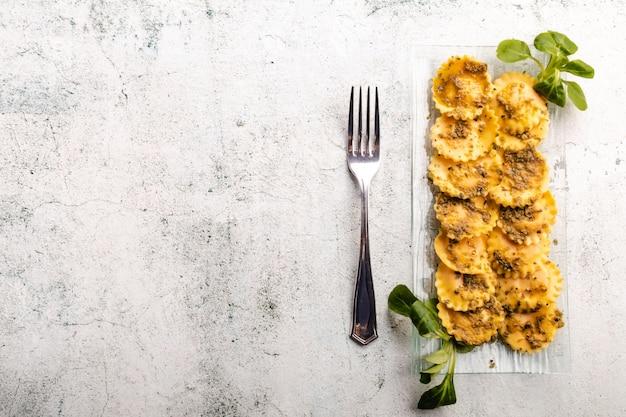 Ravioli de massa recheada italiana com fundo de molho pesto Foto Premium