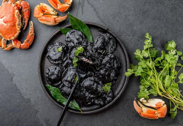 Ravioli preto italiano com camarões e caranguejos de frutos do mar na chapa preta, ardósia de pedra cinza. vista do topo Foto Premium