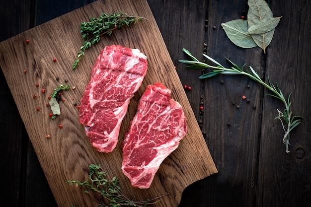 Raw chuck roll bifes premium carne com temperos na placa de madeira, vista superior, stule rústico Foto Premium