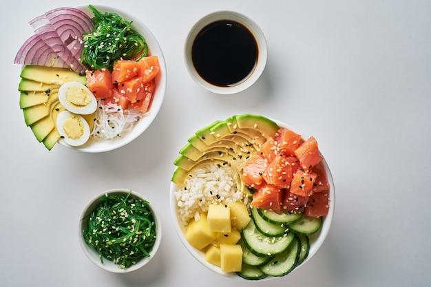 Raw poke bowl com arroz, abacate, salmão, manga, ovos de codorna Foto Premium