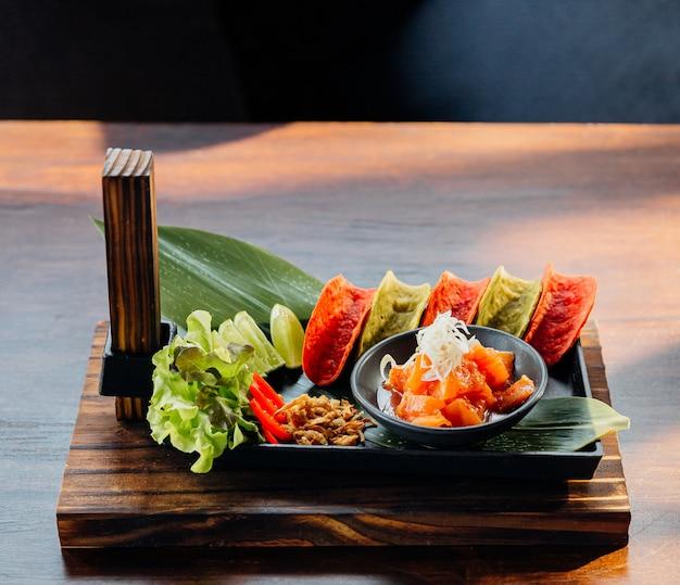 Raw salmon spicy salad servido com as microplaquetas crocantes vermelhas e verdes para o canape. Foto Premium