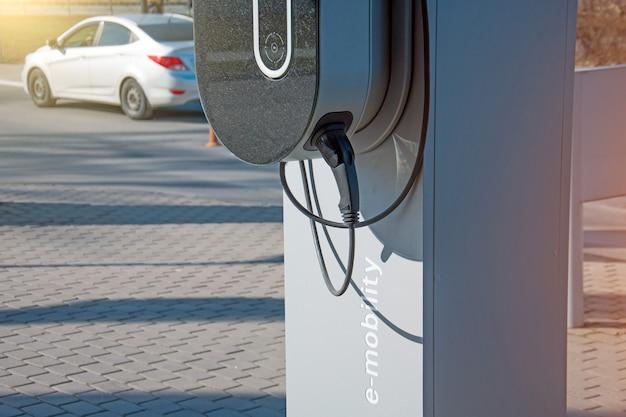 Reabastecimento para e-mobilidade de carros elétricos, o plugue elétrico sob tensão restaura a carga da bateria. Foto Premium