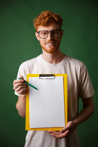 Readhead inteligente barbudo homem de camiseta branca, mostrando a pasta com copyspace Foto gratuita