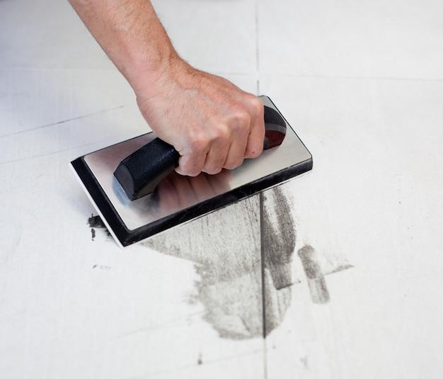 Reboco de telhas com mão de homem de espátula de borracha Foto Premium