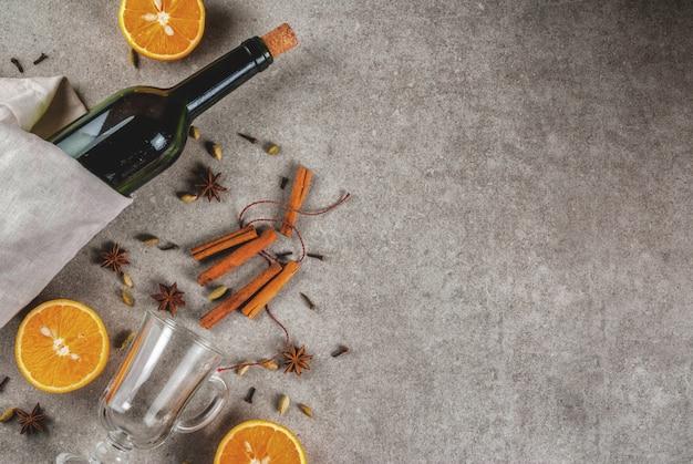 Receitas de bebidas quentes de natal, conjunto de ingredientes para vinho quente: garrafa de vinho, copos de vidro, especiarias, laranja Foto Premium