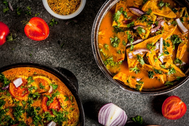 Receitas de comida indiana, omelete masala com e omelete indiano omala masala, com legumes frescos - tomate, pimenta quente, salsa pedra escura, copyspace vista superior Foto Premium