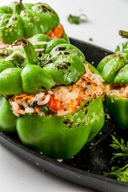 Receitas de outono. pimentão recheado caseiro com carne picada, cenoura, tomate, ervas, queijo. em branco, na assadeira, Foto Premium