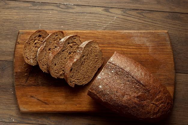Recém assado pão de centeio cortado em uma tábua de madeira Foto Premium