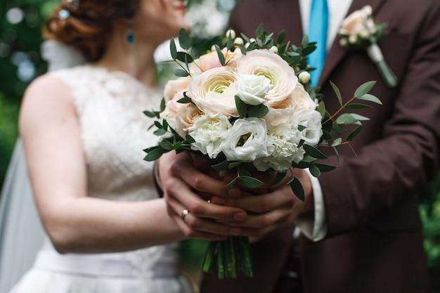 Recém-casados estão de mãos dadas no interior. buquê de rosas cor de rosa e brancas. casamento day.wedding Foto Premium