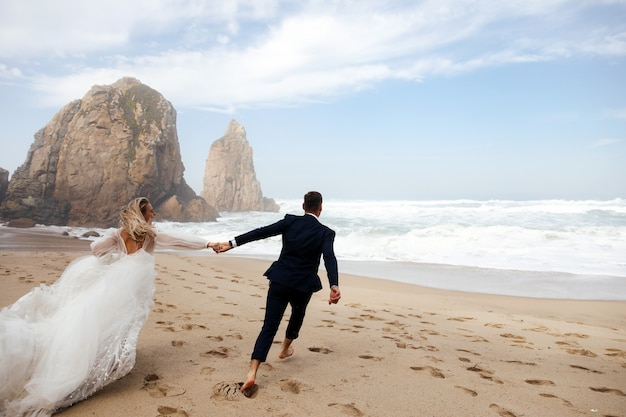 Recém-casados felizes segurando pelas mãos estão correndo pela praia no oceano atlântico Foto gratuita
