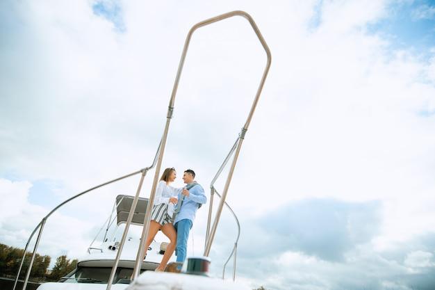Recém-casados no barco a vela com champanhe - conceito de estilo de vida alternativo exclusivo feliz. casal comemorando com champanhe em um barco, festa com a namorada de férias. Foto Premium
