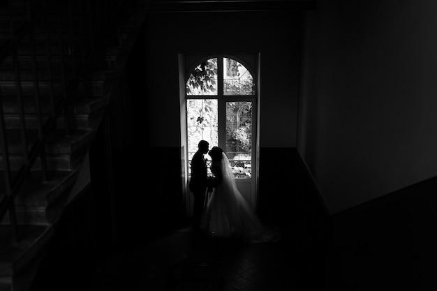 Recém-casados silhueta perto de uma janela alta em uma escada do prédio antigo Foto gratuita