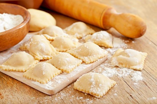 Recém-feitos caseiros deliciosos raviólis caseiros com um rolo Foto Premium