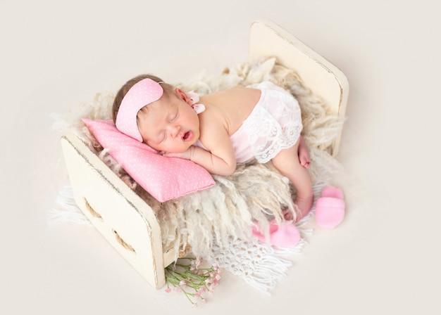 Recém-nascido dormindo na cama pequena Foto Premium