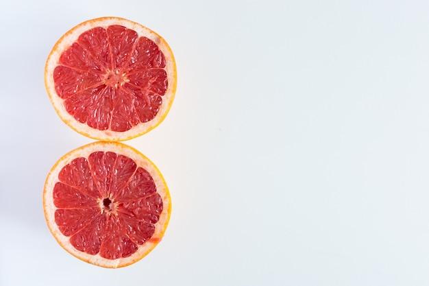 Recentemente cortada toranja ao meio em um fundo branco Foto gratuita