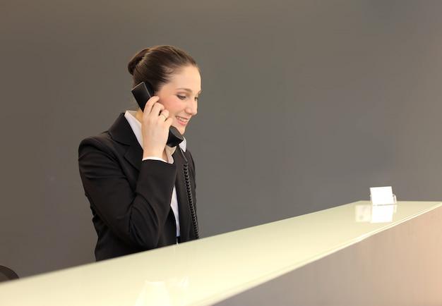 Recepcionista falando ao telefone Foto Premium