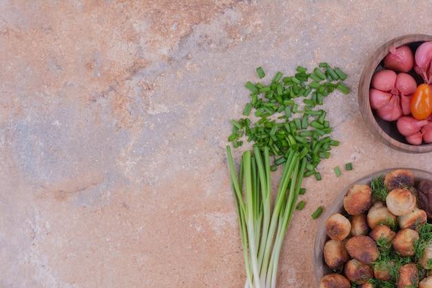 Recheios de carne servidos em um copo de madeira com ervas e alimentos marinados Foto gratuita