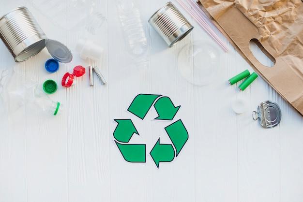 Recicl o símbolo com resíduos na mesa de madeira Foto gratuita