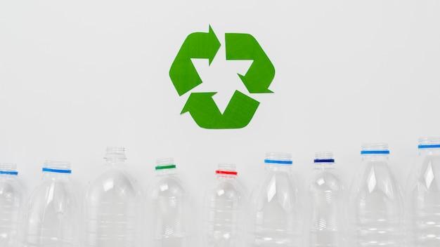 Recicl o símbolo e garrafas de plástico no backgound cinza Foto gratuita