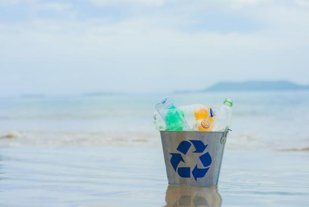 Reciclar, cesta com garrafa de plástico na praia Foto Premium