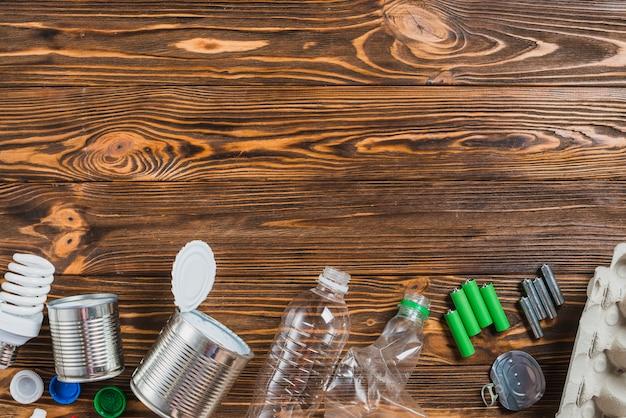 Reciclar produtos dispostos na parte inferior do fundo de madeira Foto gratuita