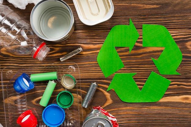 Recicle o logotipo e vários lixo reciclável na mesa de madeira Foto gratuita