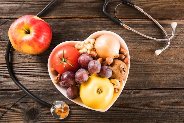 Recipiente de forma de coração com comida saudável perto de estetoscópio em fundo de madeira Foto gratuita