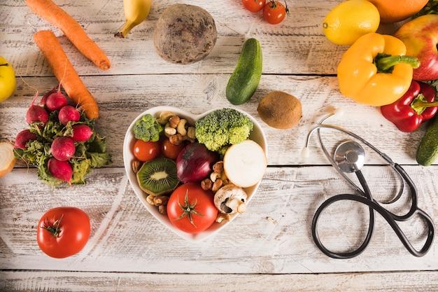 Recipiente de forma de coração com legumes saudáveis perto de estetoscópio Foto gratuita