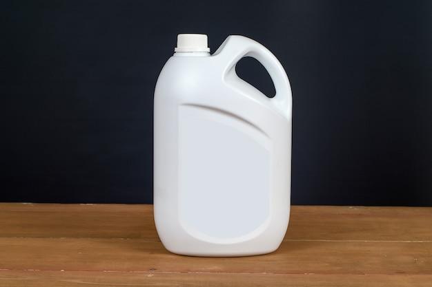Recipiente de garrafa de plástico branco na mesa de madeira. Foto Premium