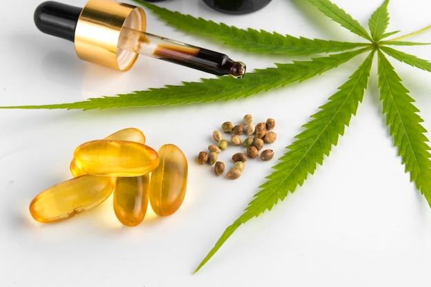 Recipiente de óleo essencial de cannabis com folhas e sementes de cannabis Foto Premium