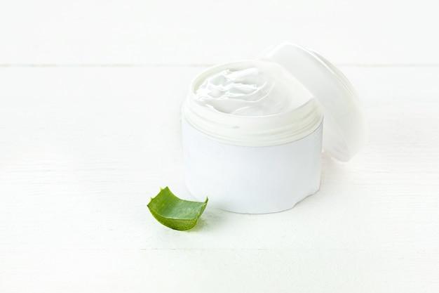 Recipiente de plástico aberto com creme e aloe Foto gratuita