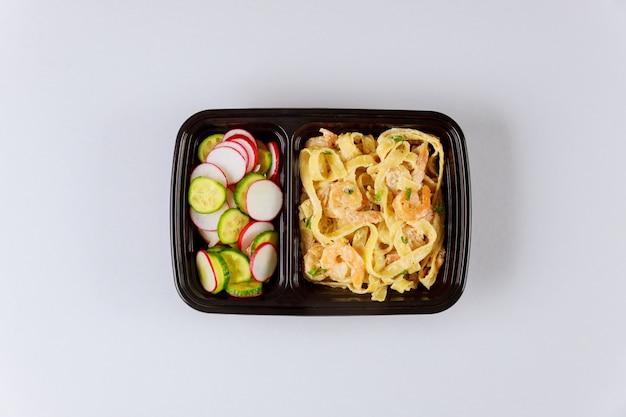 Recipiente de plástico preto com macarrão, salada e salada fresca Foto Premium